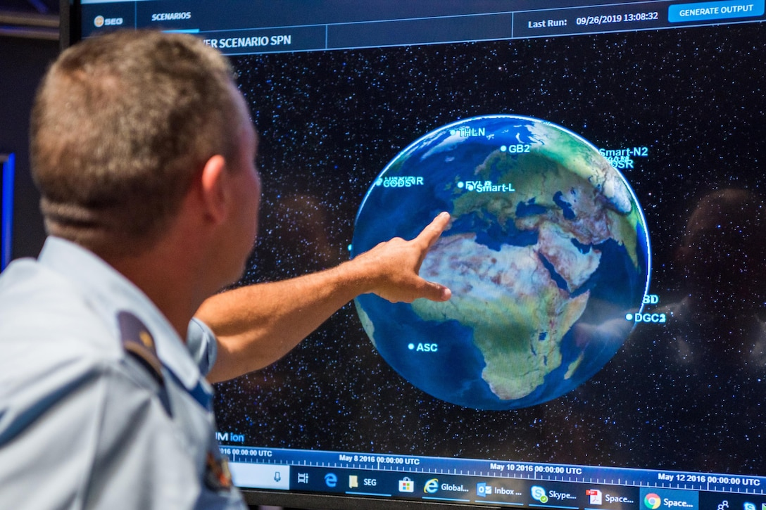 Uniformed man points at earth on wall-mounted computer screen.