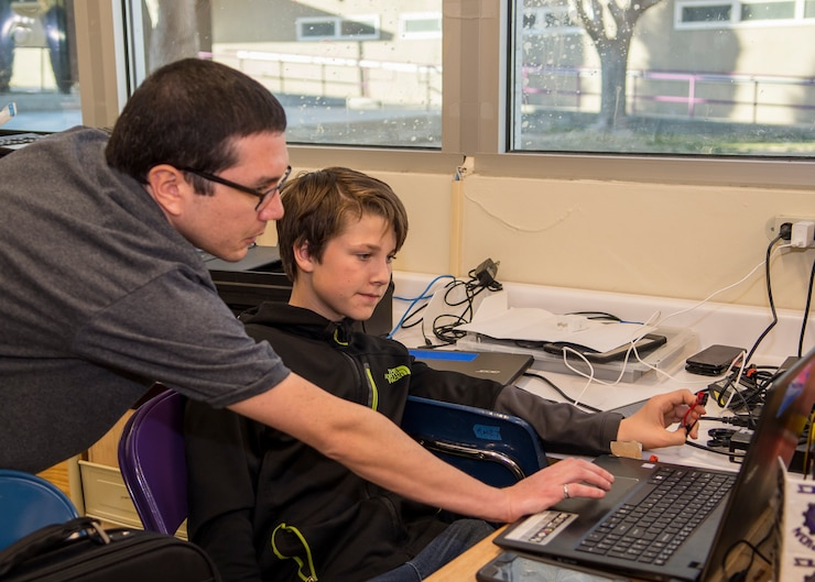 Coach Charles Eger, 773rd Test Squadron, helps Scorpion Robotics Club member Brayden Maye with computer software coding at Desert Junior-Senior High School on Edwards Air Force Base, California, Feb. 12. (Air Force photo by Giancarlo Casem)