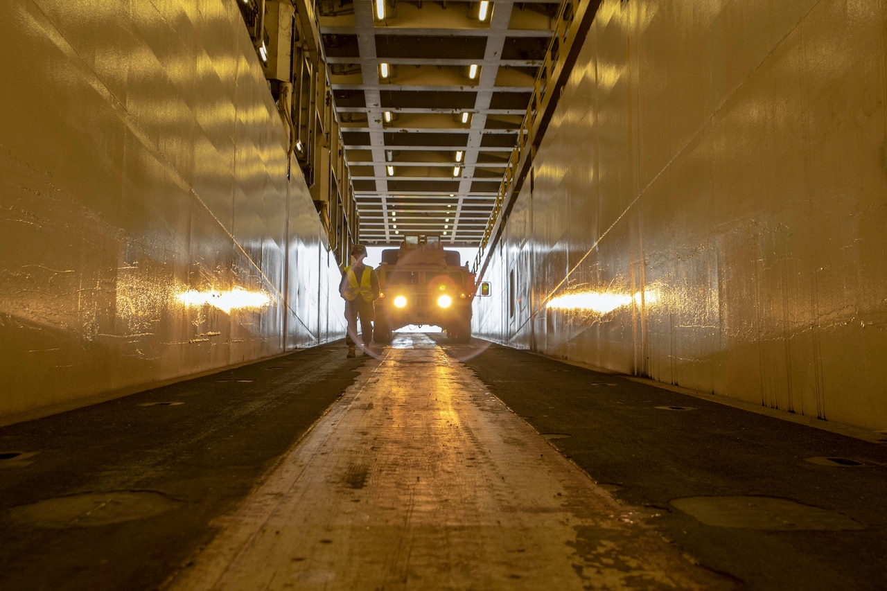 A Marine Corps vehicle is parked with headlights on aboard a cargo ship.