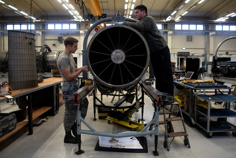 U.S. Air Force Staff Sgt. John Barickman, 52nd Maintenance Squadron aerospace propulsion craftsman, left, and Airman 1st Class Austin Wise, 52nd MXS aerospace propulsion journeyman, install an F110-GE-129 jet engine upper-fan stator case at Spangdahlem Air Base, Germany, Feb. 25, 2020. The 52nd MXS Propulsion Flight is U.S. Air Forces in Europe's sole centralized repair facility for F110 engines and is in charge of engine inspection, teardown, buildup, and testing. (U.S. Air Force photo by Airman 1st Class Valerie Seelye)