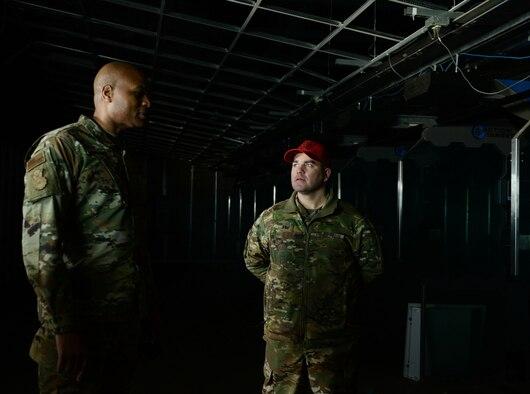 man briefs other man in dark room.
