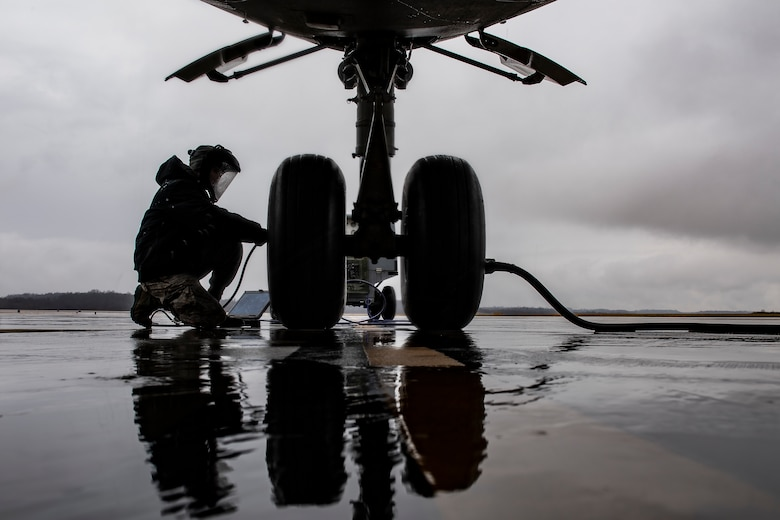 Crew chief services a nose landing-gear tire on a C-17 Globemaster III