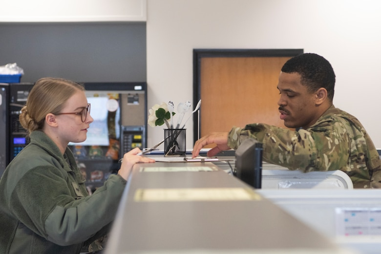 Staff Sgt. Jordan Row, 100th Logistics Readiness Squadron passenger travel and personal property supervisor, discusses travel paperwork with Senior Airman Samantha Roppo, 100th Civil Engineer Squadron commander support staff technician, Feb. 25, 2020, at RAF Mildenhall, England. The passenger travel section of the traffic management office helps organize transportation for deploying Airmen and any weapons they may carry. (U.S. Air Force photo by Airman 1st Class Joseph Barron)