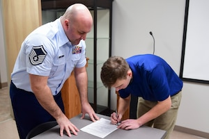 Raymond Gonzalez signs his enlistment paperwork after taking the Oath of Enlistment with Master Sgt. Christopher Beck, recruiter with the 911th Airlift Wing at the Pittsburgh International Airport Air Reserve Station, Pennsylvania, Jan. 31, 2020.