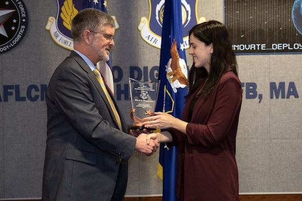 Scott Owens, deputy director of Command, Control, Communications, Intelligence and Networks Directorate, presents Kerri Hagstrom, C3I&N logistician, the Logistics Manager for ACAT I and II (non-flying) Tier I Award during an awards ceremony held at Wright-Patterson Air Force Base in Ohio and viewed by VTC at Hanscom Air Force Base, Mass., Feb.27. (U.S. Air Force photo by Jerry Saslav)