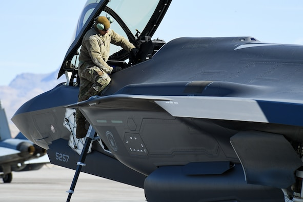 A photo of an F-35A maintainer working on the aircraft.