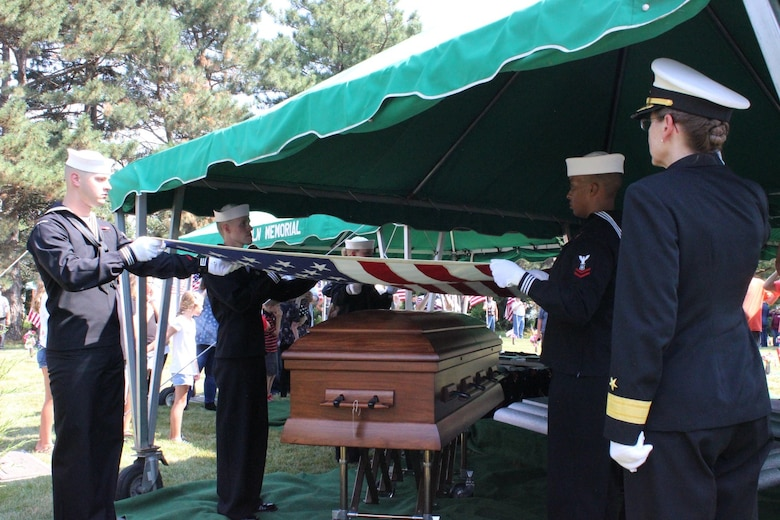 A woman in uniform salutes the flag held over a casket by navy personnel at a funeral.