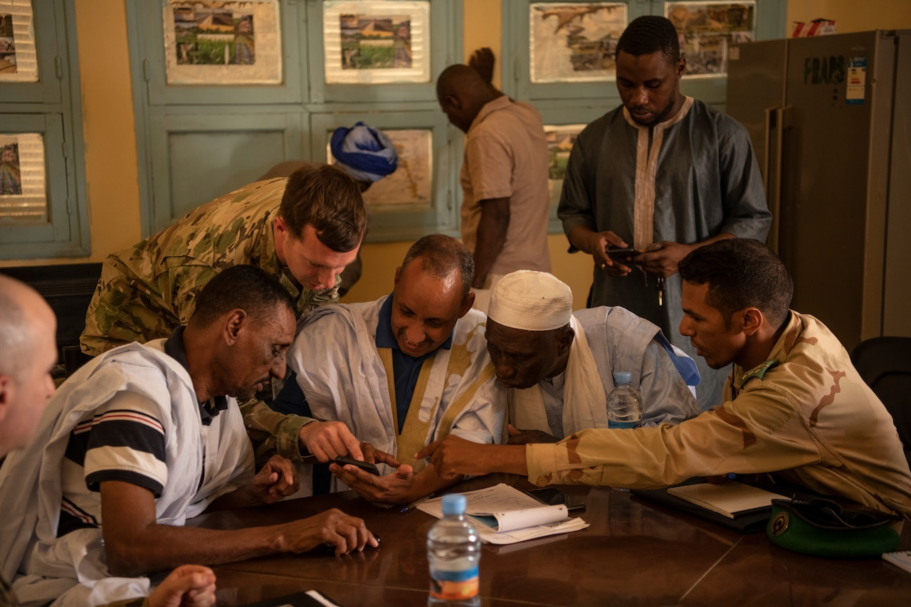 A group of men sits at a table looking at a cellphone.