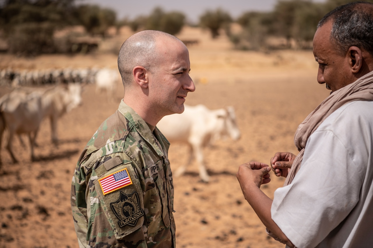A soldier talks to a man; cattle can be seen in the background.