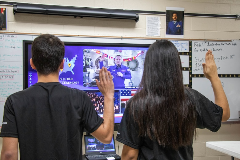 Male and female in black t-shirts with dark hair raise their right hands in front of a tv screen in a classroom.