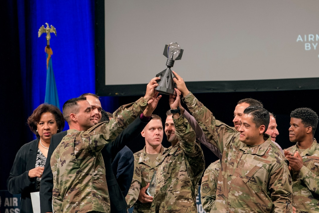 Airmen share the Spark Tank trophy after Air Force and industry leaders declared a two-way tie at the Air Force Association's Air Warfare Symposium, in Orlando, Fla., Feb. 28, 2020. The three-day event is a professional development forum that offers the opportunity for Department of Defense personnel to participate in forums, speeches, seminars and workshops with defense industry professionals. (U.S. Air Force photo by Staff Sgt. James Richardson)