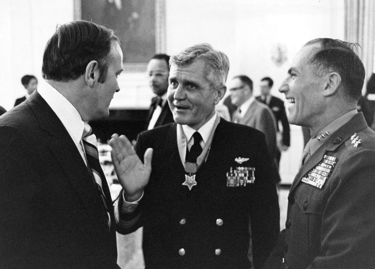Three men, two wearing military uniforms, stand talking. The man in the middle wears a medal.
