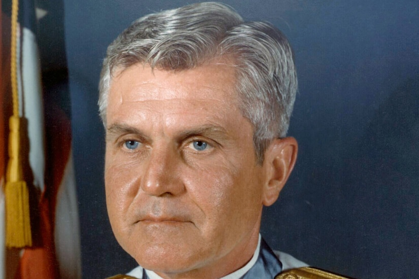 A man with gray hair sits for an official photo wearing a military uniform, a slew of medals on his chest and a Medal of Honor around his neck.