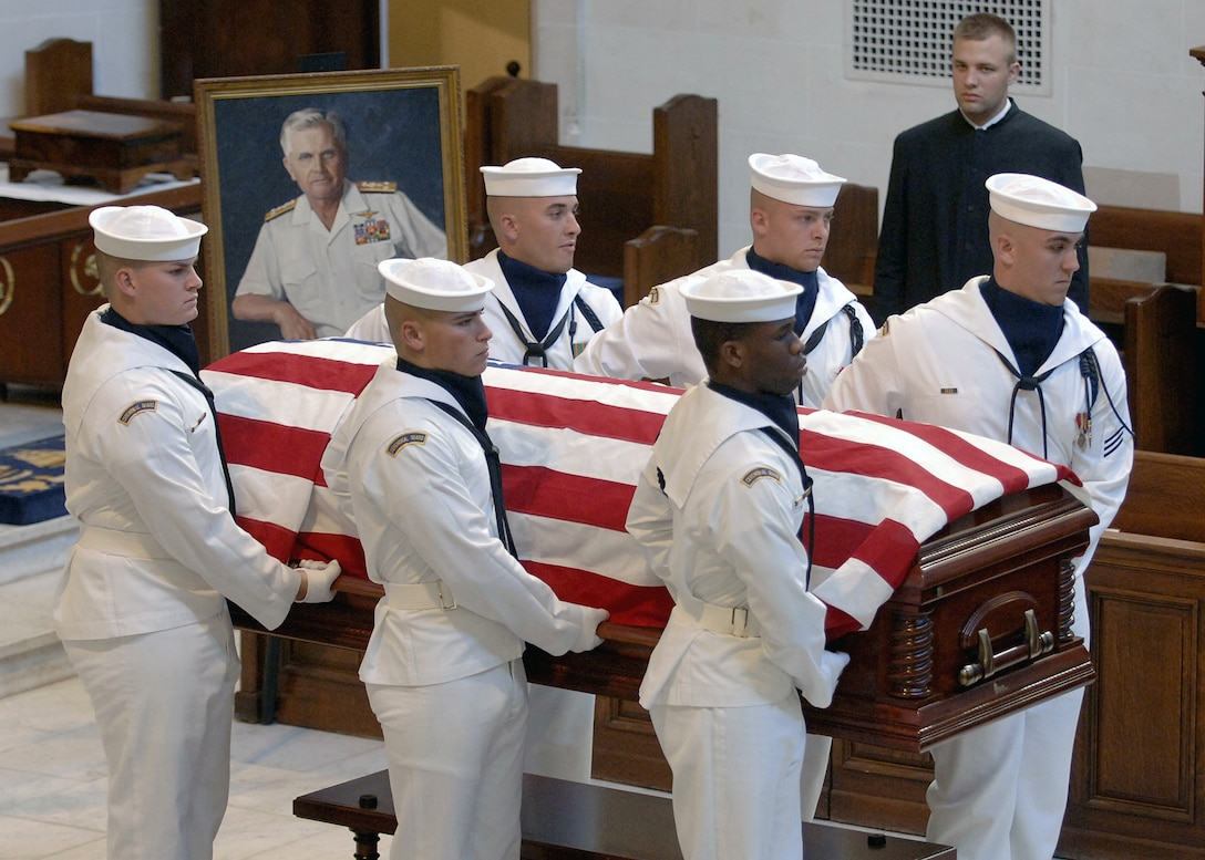 Six sailors carry a flag-draped casket. A portrait of the man who died is on display.
