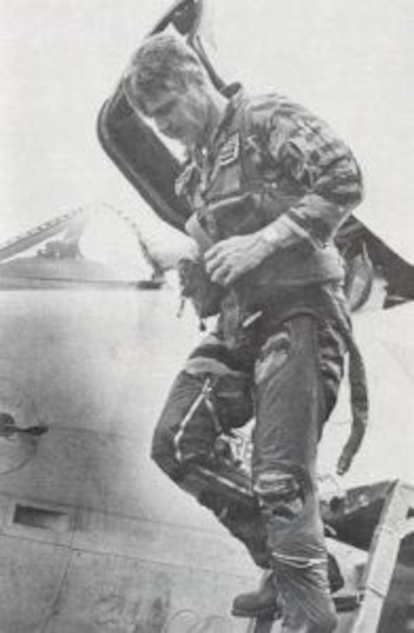 A pilot walks down the ladder off a jet's cockpit.