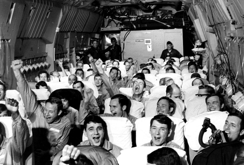A cargo airplane is packed with men, who are smiling and cheering with their hands raised.