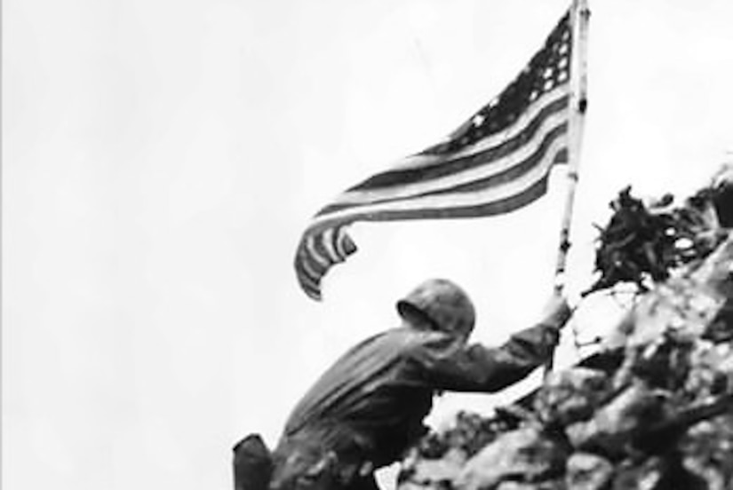 Man carries flag up rocky slope.