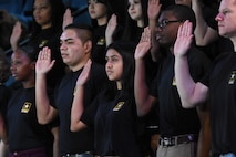 Nine young men and women of different races in black t-shirts raise their right hands.