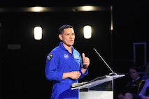 Hispanic man in blue jump suit stands in front of clear podium with microphone.