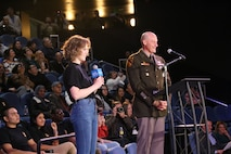 Girl with curly hair in black shirt and blue pants holds microphone standing next to man in green and kaki uniform at a black wire podium.