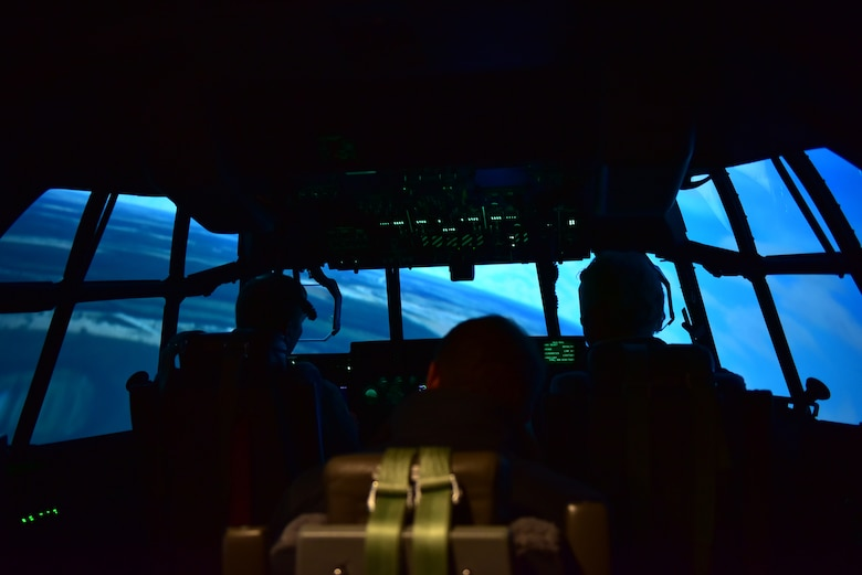 two people sit in a C-130J pilot simulator