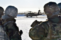 354th Security Forces Squadron defenders observe a UH-60 Blackhawk during a medical evacuation exercise on Eielson Air Force Base, Alaska, Feb. 26, 2020. Defenders loaded a simulated casualty into the aircraft and rode in the Blackhawk to familiarize themselves with the aircraft. (U.S. Air Force photo by Senior Airman Beaux Hebert)
