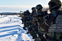 354th Security Forces Squadron defenders simulate an ambush during a medical evacuation exercise on Eielson Air Force Base, Alaska, Feb. 26, 2020. The defender's M4 carbines are equipped with a blank-firing adaptor to simulate the sound of a gunshot without any projectiles. (U.S. Air Force photo by Senior Airman Beaux Hebert)