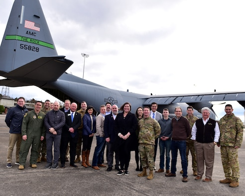 a group poses for a photo in front of a C-130J
