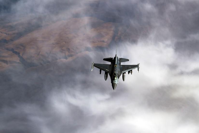 Fighter plane flies over rough terrain.