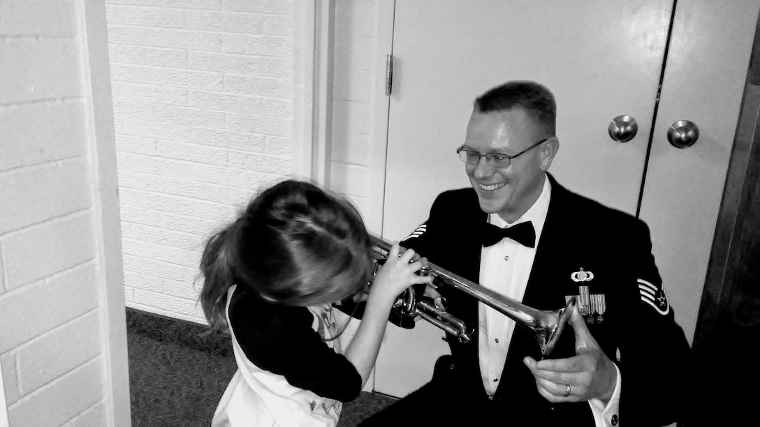 Staff Sergeant Dan Thrower, trumpet player with the USAF Heartland of America Band, demonstrates his instrument to a young audience member during an Offutt Brass concert intermission.