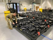 Staff Sgt. Zachary Casey helps unload the plastic crates containing the new Army Combat Fitness Test (ACFT) equipment onto the USPFO warehouse floor Dec. 11, 2019. (Photo Credit: Staff Sgt. Benjamin Crane)