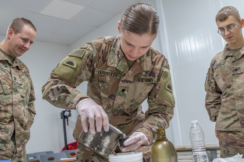 U.S. Army Spc. Shelby Vermeulen (center), with 1st Squadron, 303rd Cavalry Regiment, 96th Troop Command, Washington Army National Guard, works through the steps of water purification during a Field Sanitation Team Certification Course held from Dec. 9 to Dec.13, 2019 at Joint Training Center-Jordan. Soldiers must be ready and capable to conduct the full range of military operations to defeat all enemies regardless of the threats they pose. (U.S. Army photo by Shaiyla B. Hakeem)