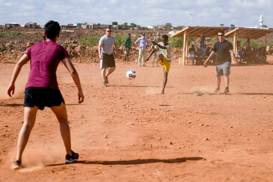 Service members in civilian clothes play soccer with villagers on a dirt field.