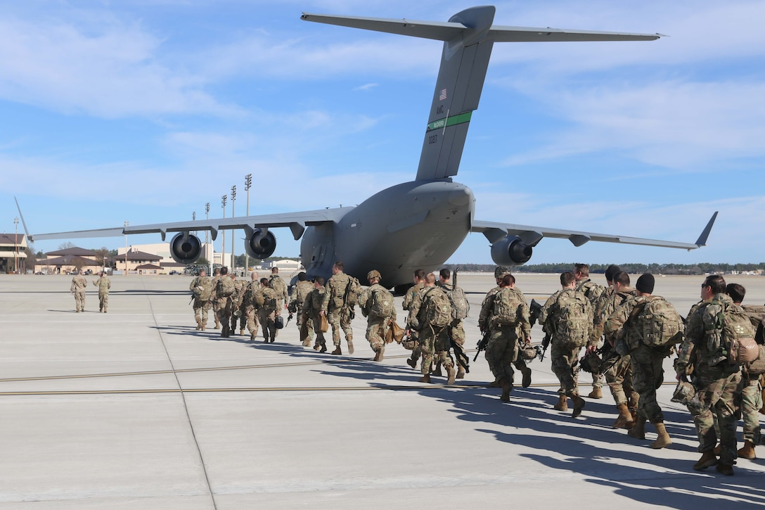 Soldiers line up to get on a military aircraft.