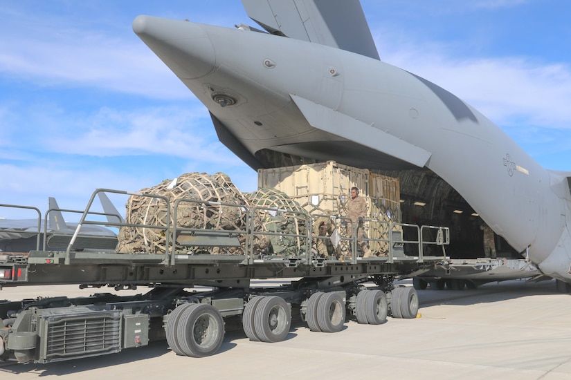 Cargo is loaded into the back end of a military aircraft.