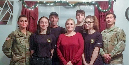 five siblings, two in uniform and both parents pose for a family photo.