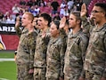 group of men and women in Army uniforms hold up their right hands and take the oath of enlistment.
