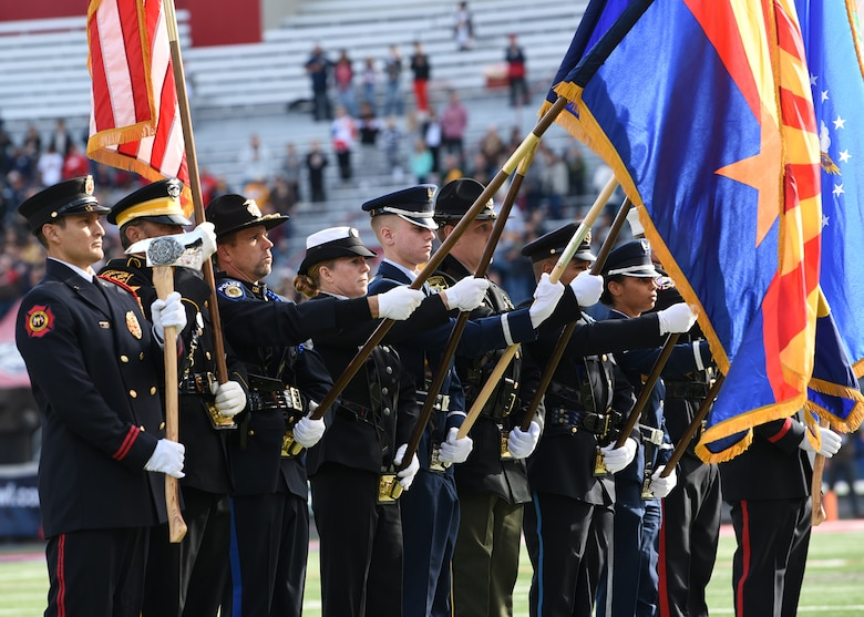 photo of U.S. servicemembers and first responders presenting the colors during the national anthem at the Arizona Bowl football game