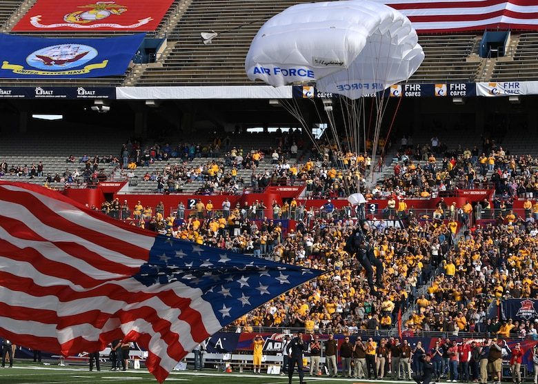 Photo of a U.S. Air Force skydiving team member parachuting with a U.S. flag onto a football field