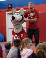 Dan Meers, the Kansas City Chiefs NFL team mascot KC Wolf, demonstrated how he gets dressed for work by allowing a volunteer to wear his suit at the Youth Center, Whiteman Air Force Base, Missouri, Dec. 18, 2019. Meers talked to the children about the importance of your attitude, behavior and character and answered questions about what life is like as a mascot as part of an outreach to positively influence their overall well-being and promote resiliency. (U.S. Air Force photo by Airman 1st Class Christina Carter)