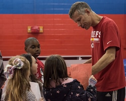 Dan Meers, the Kansas City Chiefs NFL team mascot KC Wolf, receives pictures made by the children at the Youth Center, Whiteman Air Force Base, Missouri, Dec. 18, 2019. Meers talked to the children about the importance of your attitude, behavior and character and answered questions about what life is like as a mascot as part of an outreach to positively influence their overall well-being and promote resiliency. (U.S. Air Force photo by Airman 1st Class Christina Carter)