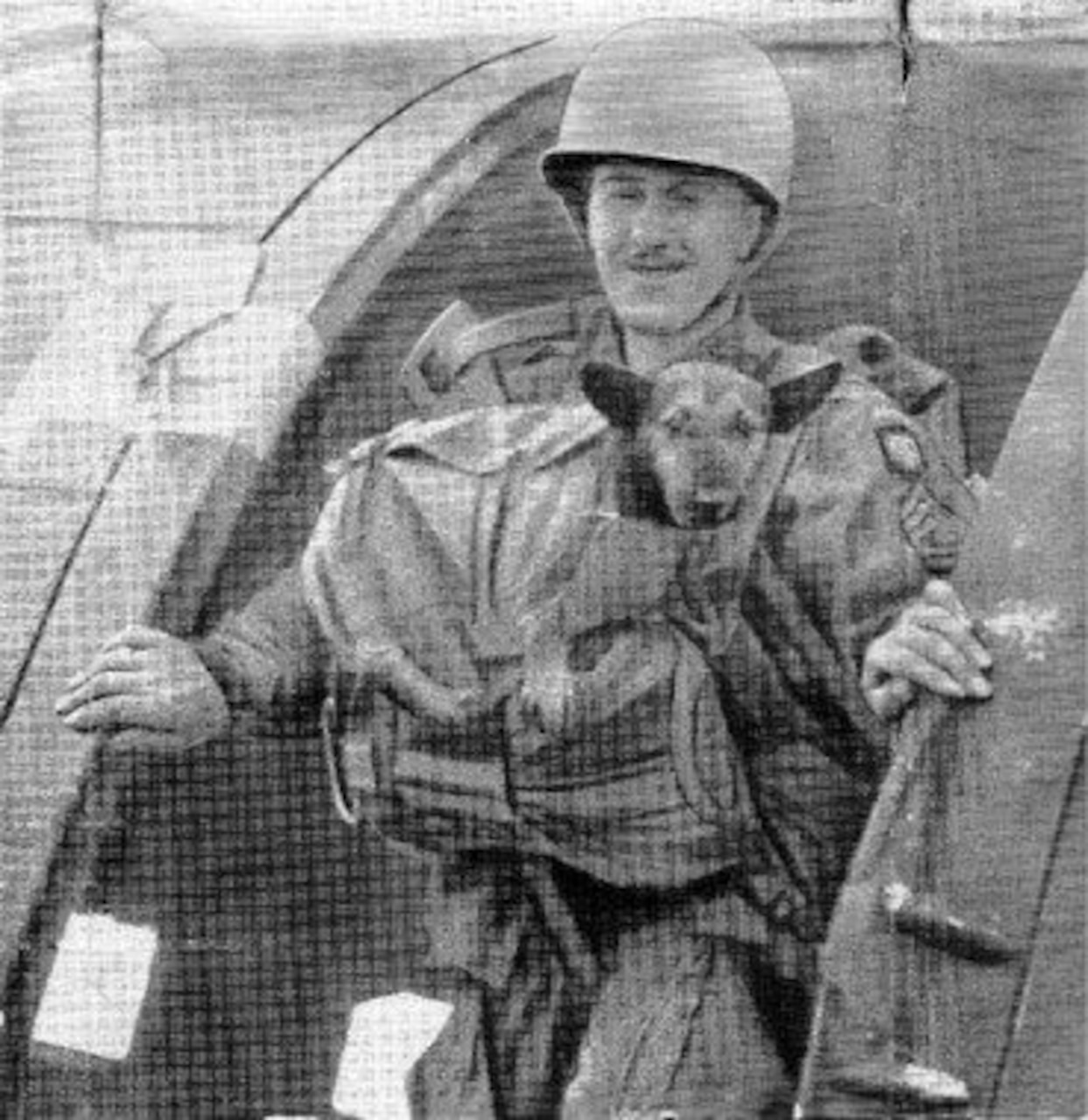 A World War II paratrooper wearing a combat helmet and parachute gear has an 8-month-old puppy strapped to his chest. Both stand at the open door of an airplane.