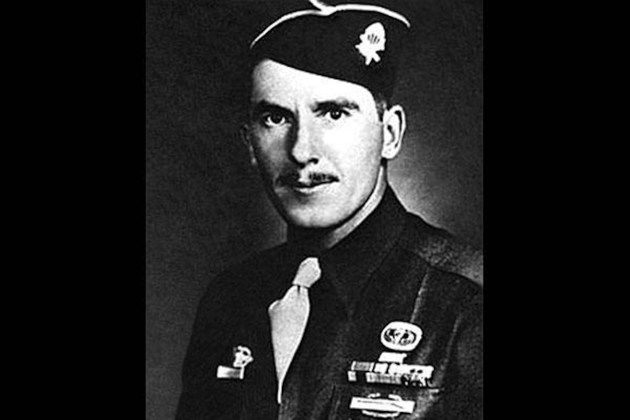 A soldier in dress cap and jacket with ribbons poses for an official photo.