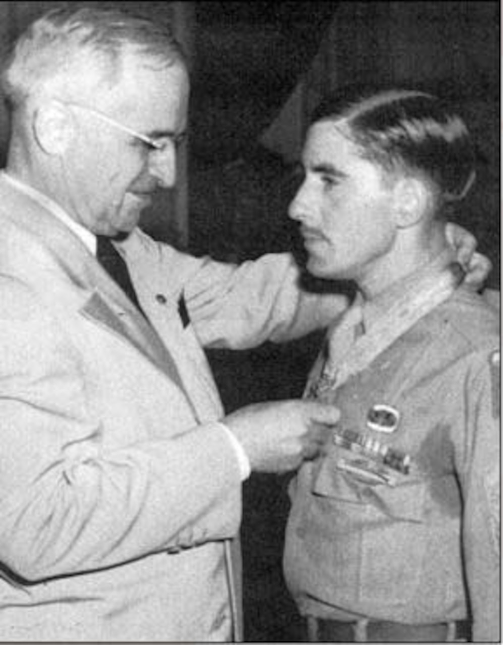 President Harry S. Truman places the Medal of Honor around the neck of a soldier who stands at attention.