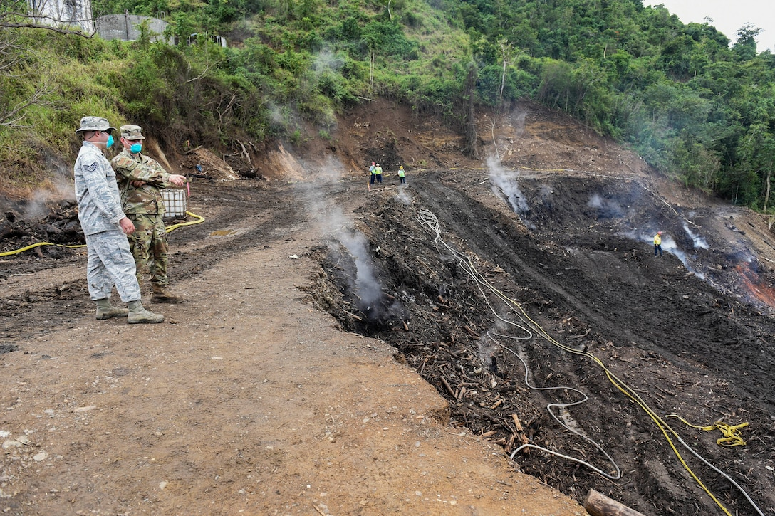 Two airmen wearing protective masks look at a smoldering patch of ground.