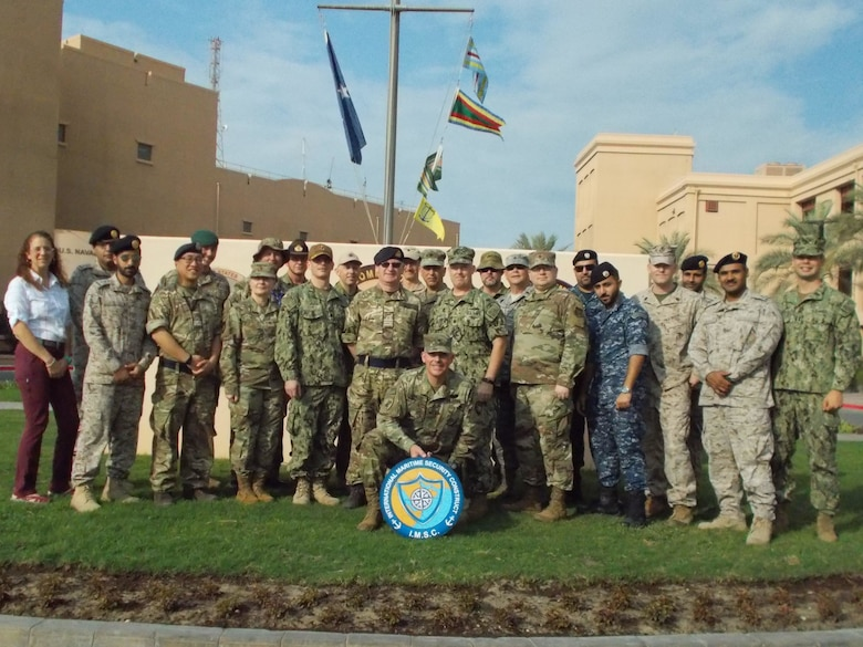U.S. Army Reserve Col. John Conklin, center, poses for a photo with service members and a DoD civilian from the Joint Planning Support Element and members of the International Maritime Security Construct in front of the Combined Maritime Forces Headquarters, Naval Support Activity, Bahrain, Nov. 25, 2019.