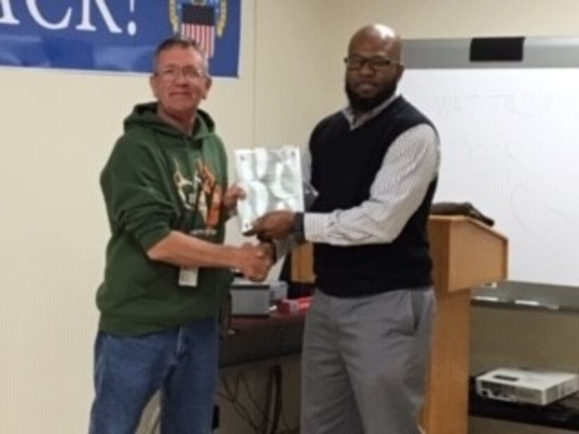 Operations Chief Willie Mitchell presents Disposal Service Representative Dave Smith with a plaque from Veterans Administration for helping the agency find usable items to aid homeless vets.