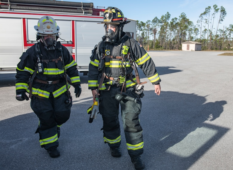 U.S. Air Force Col. Brian Laidlaw, 325th Fighter Wing commander (left), walks with U.S. Air Force Senior Airman Christian Gosnell, 325th Civil Engineer Squadron driver operator (right), to a simulated burning building exercise at Tyndall Air Force Base, Fla., Dec. 20, 2019. Laidlaw joined Gosnell and the 325th CES fire team to experience fire fighting first hand. (U.S. Air Force photo by Senior Airman Stefan Alvarez)
