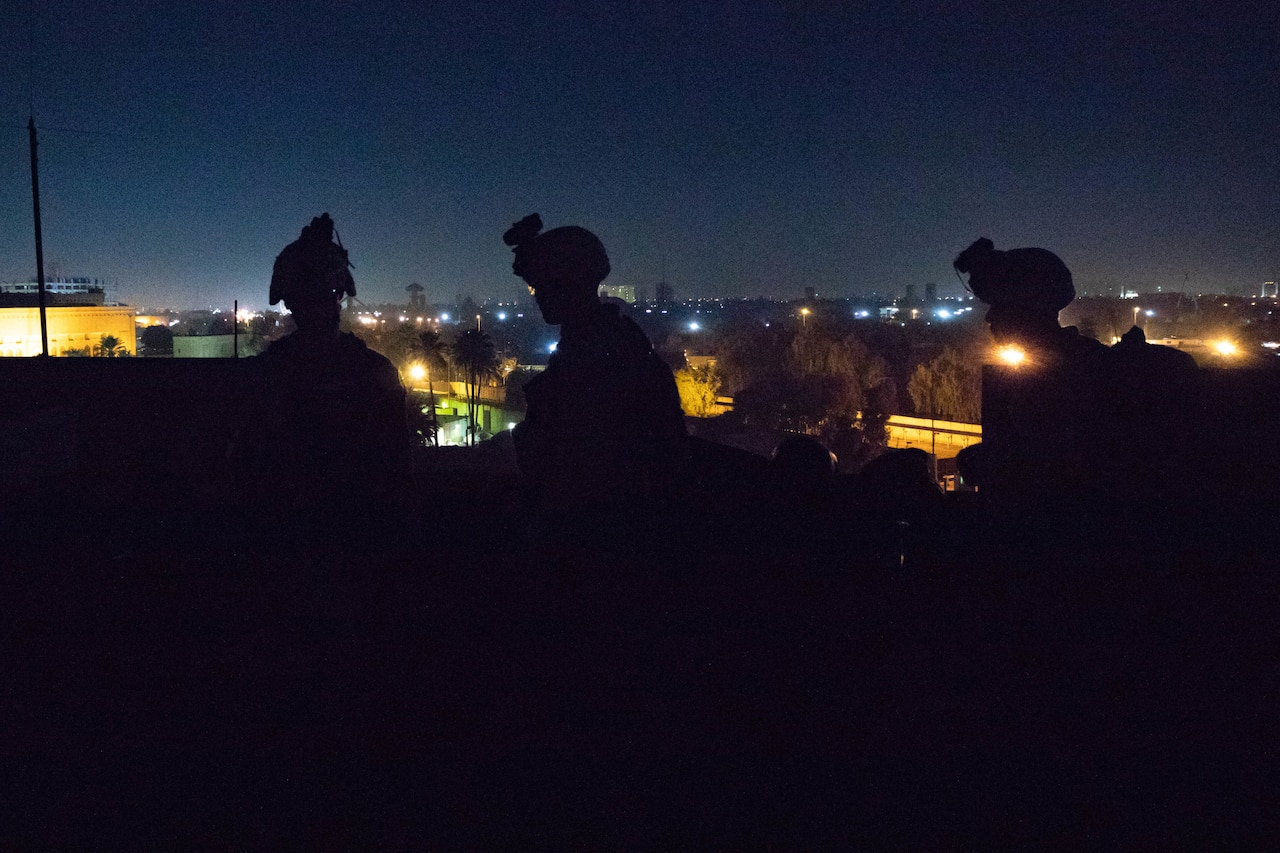 Three Marines wearing combat equipment are silhouetted against a city skyline at night.