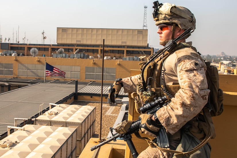 A Marine with combat gear stands watch on top of a building. A U.S. flag is in the background.